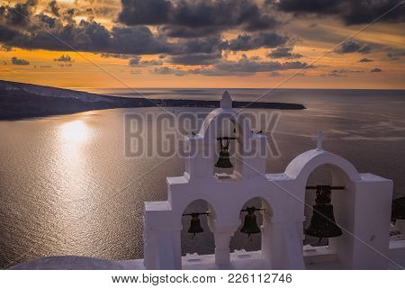 Romantic Sunset With Church Belfry In Front.. Oia Village, Santorini, Greece