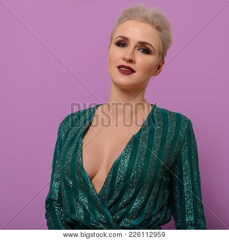 Portrait Of A Young Woman With A Short Haircut In A Green Evening Dress With A Deep Neckline On A Pu