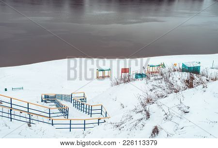 Snow-covered Playground On The River Bank In Winter. Snowy Hills Next To The River Ridge To The Rive