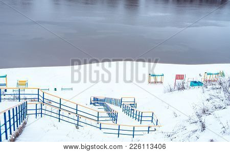 Birch Winter River In The City. Snow-covered Playground On The River Bank In Winter. Snowy Hills Nex