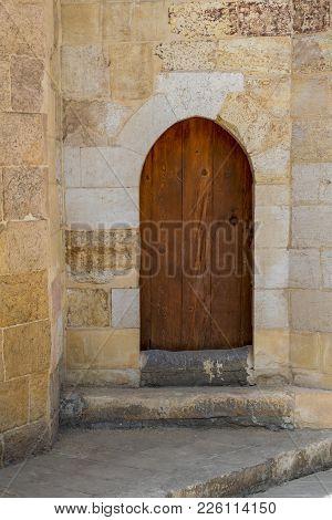 Grunge Wooden Aged Vaulted Door On Exterior Stone Bricks Wall Of Amir Aqsunqur Mosque (blue Mosque),