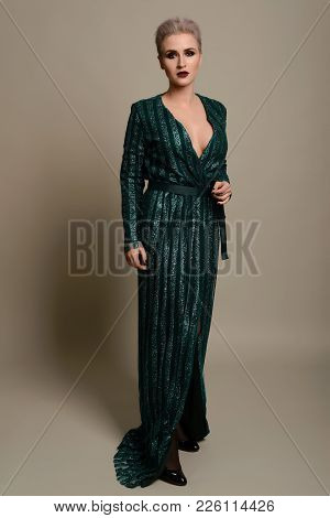 Beautiful Young Woman Dressed In Stylish Turquoise Blue Bandeau Maxi Dress Posing On Background.