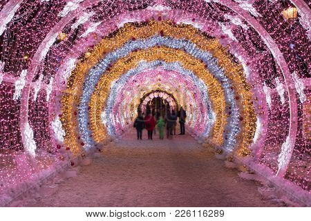 People Walking Through The New Year And Christmas Holidays Light Tunnel In The City Center In Moscow