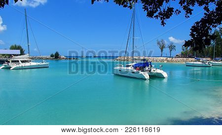 A marina with catamarans and sailing boats with blue water and a stone quay in a beautiful bay on the Seychelles, a paradise postcard feeling poster