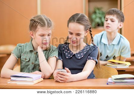 Schoolkid Girl Shows Cell Phone To Her Friends