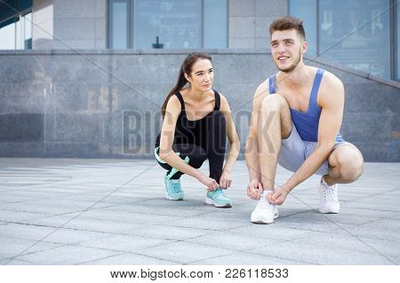 Happy Man And Woman Tying Shoelaces On Sneakers Before Running, Getting Ready For Jogging In City Ce