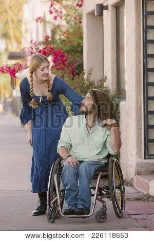Woman Talking With Friend In Wheelchair On Sidewalk