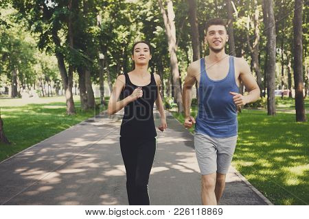 Young Happy Sporty Woman And Man Jogging In Green Park During Morning Workout, Copy Space