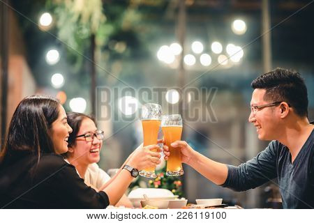 Group Of Asian Friends Or Coworkers Cheering With Beer, Celebrating Together At Restaurant Or Night