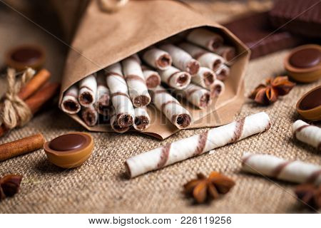 Sweet Wafers Rolls,  Caramel Candies And Chocolate On A Burlap Background