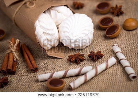 Zefir, Sweet Wafers Rolls And Caramel Candies On A Burlap Background