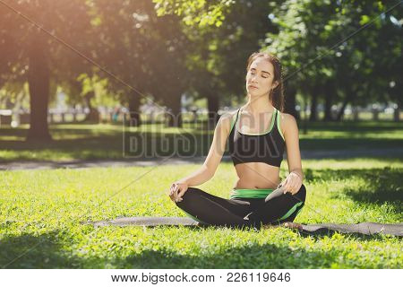 Young Woman Outdoors, Meditation Exercises. Girl Doing Lotus Pose For Relaxation With Closed Eyes. W