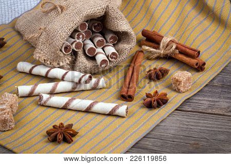 Sweet Wafers Rolls,  Caramel Candies And Sugar On A Wooden Table