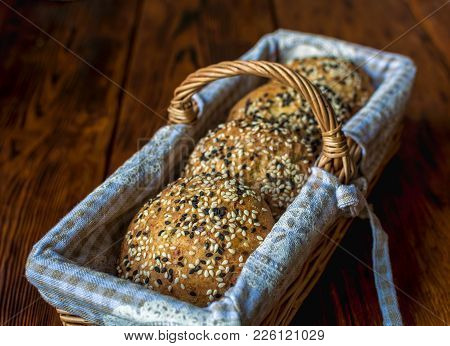 Wicker Basket With Bread. Bread And Buns Inside Basket. Fresh Bakery Products On Table. Tastes Best