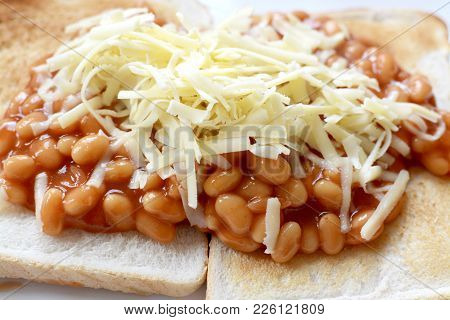 Baked Beans On White Toast Topped With Grated Cheddar Cheese