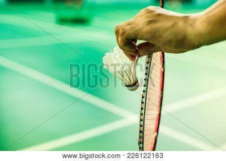 Closeup Badminton Player Hand Holding The Shuttle Cock Together With The Racket, Ready To Serve Posi