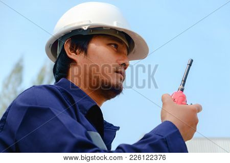 Asian Engineer In Blue Safety Uniform And White Security Helmet Using Walkie-talkie On Blurred Indus