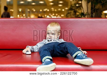 Child Is Lying On The Couch In The Shopping Center Or Mall. Little Boy Tired During Shopping With Pa