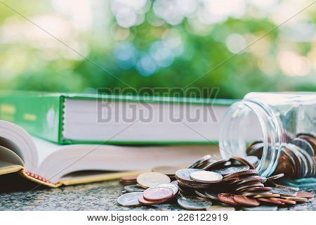 Pile Of Money Coins In The Glass Jar With Book On Blurred Natural Green Background And Added Colour