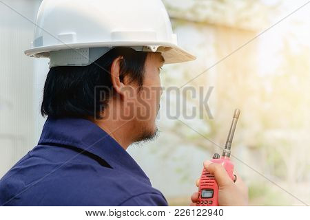 Asian Engineer In Blue Collar Safety Uniform And White Security Helmet Using Walkie-talkie On Blurre