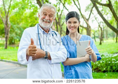 Portrait Of Doctor With A Stethoscope And Nurse Showing Thumbs Up In Park At Hospital