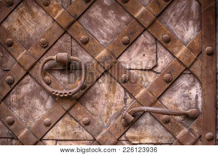 Fragment Of The Old Iron Door. Forged Handle On The Background Of Metal Doors