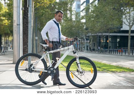 Businessman Walking With Bicycle On Urban Street And Looking At Camera. Serious Young Latin Man In F
