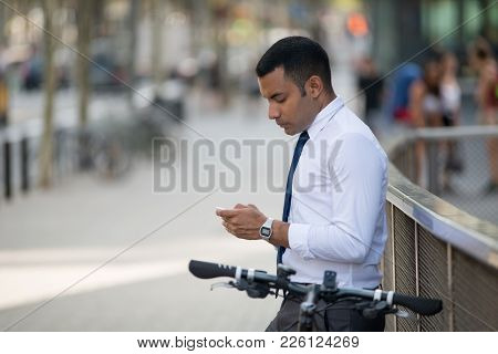 Calm Latin Male Manager Texting Message On Phone Outdoors While Standing Near Railing With Bicycle.