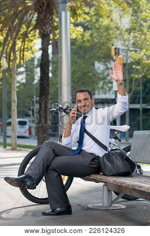 Cheerful Young Latin Businessman Waving Hand To Colleague While Waiting Him In Urban Park. Positive