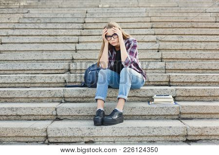Desperate Student Girl Sitting On Stairs Outdoors In University Campus. Woman Raised Hands To Her He