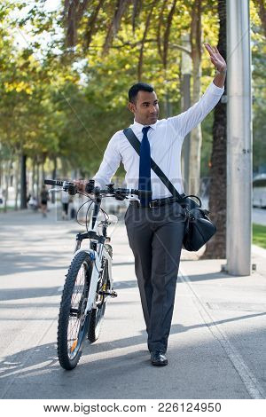 Handsome Postman Walking With Bike On Street And Waving Hand While Greeting Neighbor. Content Young