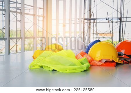 White, Orange, Yellow And Blue Safety Helmet With Reflective Clothing On Desk At Construction Site A
