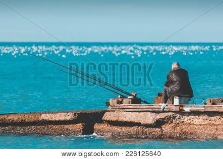 An Elderly Lonely Man Is Fishing On A Sea Pier. Old Age And Loneliness.