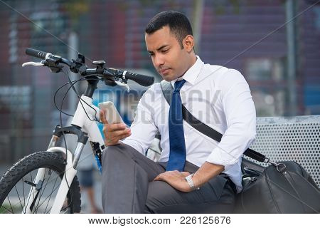 Serious Young Hispanic Businessman Reading Sms On Stroll. Concentrated Latin Office Employee Surfing