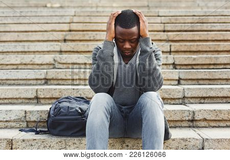 Desperate African-american Student Sitting On Stairs Outdoors In University Campus. Man Raised Hands