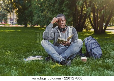 Desperate African-american Student Reading Book In Park, Preparing For Exams At University Or Colleg