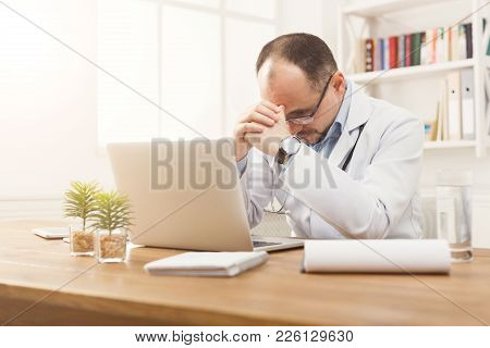 Portrait Of Tired Doctor In Glasses Sitting At The Desktop. Physician Is Working In Bright Office, M