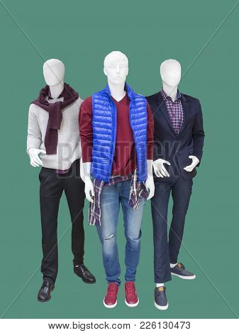 Three Full Length Male Mannequins Dressed In Casual Clothes Isolated On Green Background. No Brand N