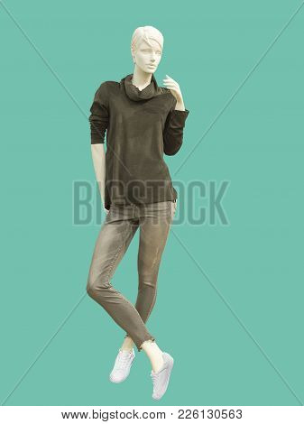 Full-length Female Mannequin Dressed In Casual Clothes Over Green Background. No Brand Names Or Copy
