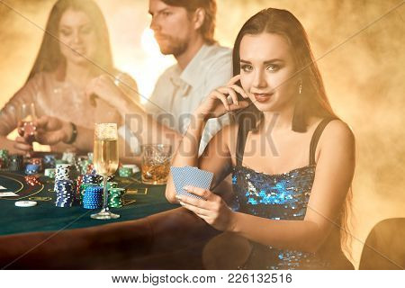 Group Of An Elegant People Playing Poker At The Gambling House. Focus On A Luxurious Brunette In A B