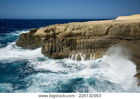 Malta, Gozo Island Rocky Shore, Blue Sky And Sea With Foamy Stormy Clouds