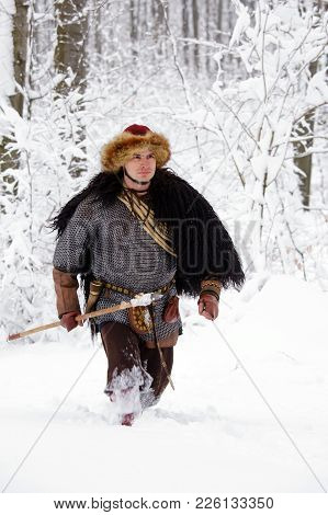 Viking Warrior With Chain Mail Leather Spear Walking In Winter Woods Before Battle, Scandinavian Tra