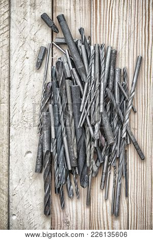 Old Drill Bits On A Wooden Background