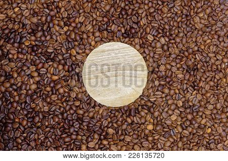 Round Wooden Board Lying In The Roasted Coffee Beans