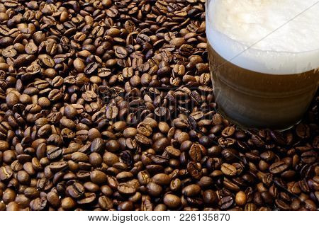 Roasted Coffee Beans And A Cup Of Coffee In The Corner Of The Picture