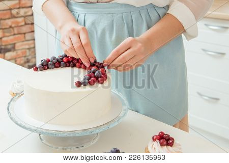 Women's Hands Decorated With Red And Blue Berries White Birthday Cake