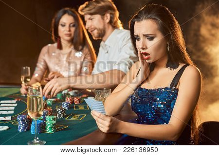 Group Of An Elegant People Playing Poker At The Gambling House. Focus On A Emotional Brunette In A B