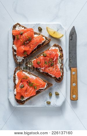 Smorrebrod, traditional Danish open sanwiches, dark rye bread with salmon, cream cheese and capers. Top view. poster