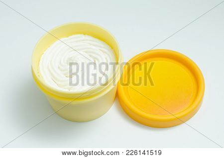 Open Yellow Cream Jar With White Lotion Isolated On White Background. Skin Care Product Package. Opa