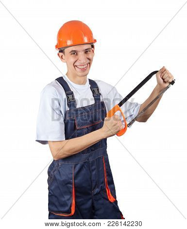 A Young Worker In A Helmet Holds A Hacksaw And Smiles Into The Camera. Image For Advertising Works O